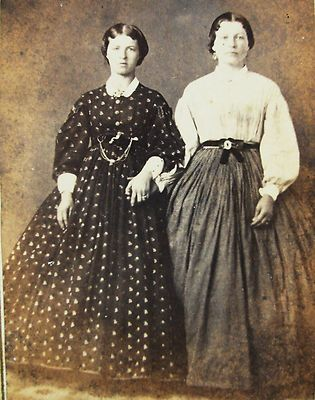 1850s, the woman on the right is wearing a white blouse with voluminous sleeves.