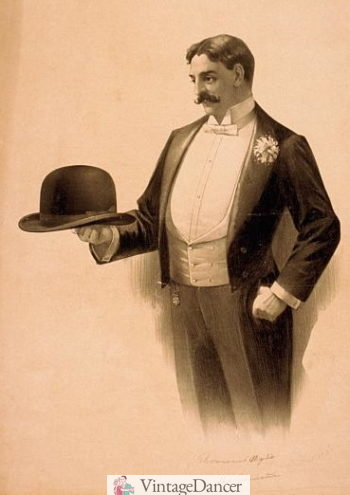 1896 tailcoat, white shawl vest, and white chrysanthemum boutonnière. Holding a derby hat.