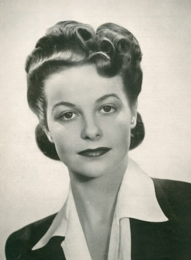 1943, hair gathered and waved with some curls on top, rolled under into a chigon on the bottom